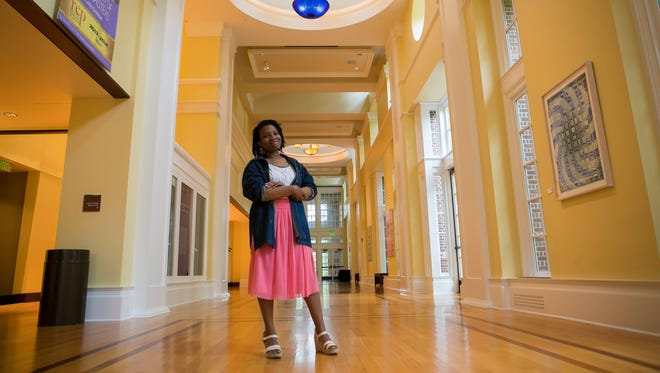 June Pressley stands in the lobby area of the Center for the Arts on the UD campus. Pressley is graduating this spring after simultaneously getting two degrees from UD and DSU.