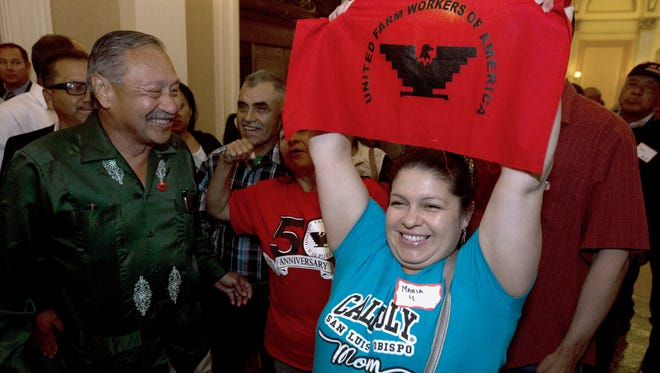 FILE -- In this Aug. 29, 2016 file photo Maria Ceja, right, joined other farm workers in celebrating outside the Assembly Chambers after lawmakers approved a measure requiring farmworkers to receive overtime pay after working eight hours, at the Capitol, in Sacramento, Calif. In a unanimous ruling Monday, Nov. 27, 2017, the high court in California upheld a law that aims to get labor contracts for farm workers whose unions and employers do not agree on wages and other working conditions.