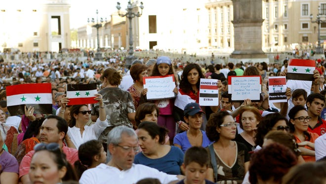 People hold Syrian flags and signs against a possible attack to Syria, prior to the start of a vigil for peace attended by Pope Francis in St. Peter's Square at the Vatican, Saturday, Sept. 7, 2013.
