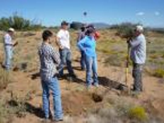 Students in the New Mexico State University Range Club help with a mass shrub-planting project at the C Bar Ranch southwest of Silver City.