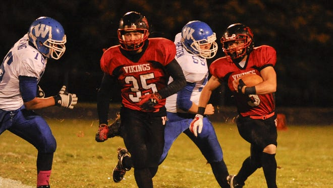 Valders' running back No. 3 Paxton Korslin rushes for a first down as he follows blocker No. 35 Alex Jirschele against Wrightstown during the first quarter of the varsity football game at Valders High School on Oct. 17, 2014.