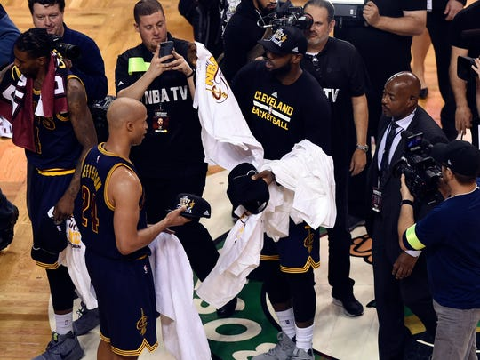 LeBron James passes out t-shirts after defeating the Boston Celtics in game five of the Eastern conference finals of the NBA Playoffs at TD Garden. Mandatory