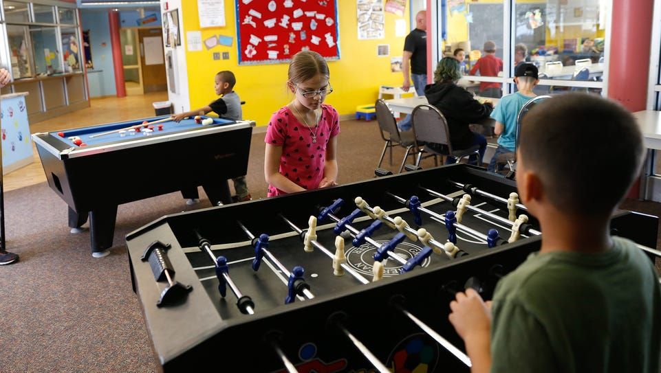 At center, Ailee Samora plays table soccer with Xavier