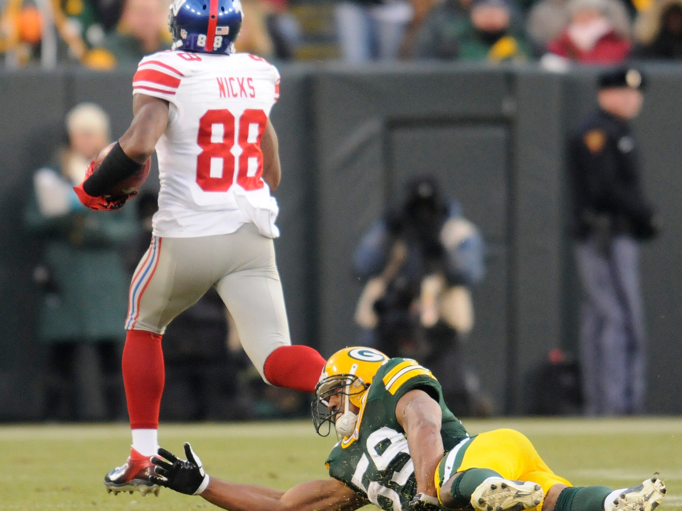 Green Bay Packers linebacker Brad Jones (59) falls as receiver Hakeem Nicks (88) runs away in the first quarter against the New York Giants during the NFC divisional playoff game at Lambeau Field in Green Bay on Sunday, Jan. 15, 2012.