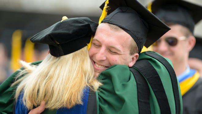 Kurt Jansen of Wrightstown hugs one of his professors after Sunday's graduation ceremony.
