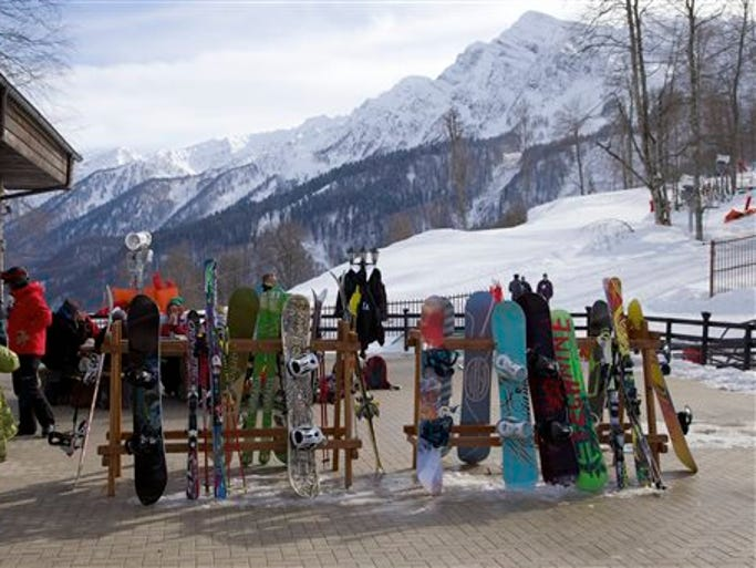 In this Wednesday, Feb. 6, 2013, file photo, snowboarders and skiers rest after competitions, in Rosa Khutor, some 60 km east of the Black Sea resort of Sochi, Russia.