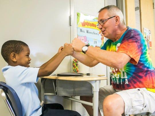 Tutor Alan Dubs fist-bumps first-grader Jaylen Laboriel,