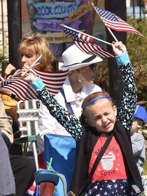 Lola Tarkowski of Oconomowoc waves four flags at a time during last year's Maifest parade.