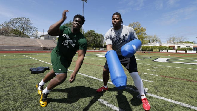 """Michael Dwumfour, left, and Rashan Gary work out in New Jersey in April. The incoming defensive linemen have """"known each other since sixth grade,"""" Dwumfour said. """"He'll definitely be coming to my dorm room a lot."""""""