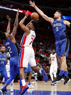 Pistons forward Stanley Johnson (7) attempts a shot against Magic guard Elfrid Payton (2) and center Nikola Vucevic (9) during the third quarter of the Pistons' 114-110 win on Sunday, Dec. 17, 2017, at Little Caesars Arena.