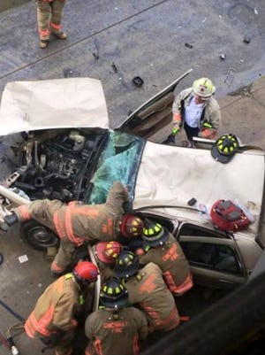 Cincinnati firefighters try to extricate someone after a car plowed into a Camp Washington building Tuesday.