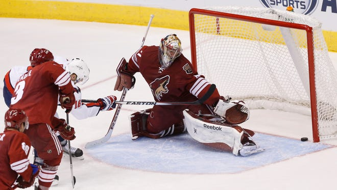 Washington Capitals forward Eric Fehr (left) shoots his game-winning goal against Arizona Coyotes goalie Mike Smith in OT for a 2-1 victory at Gila River Arena in Glendale November 18.