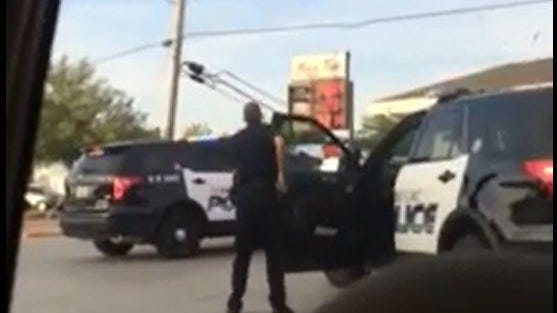 A screenshot shows a Fond du Lac Police officer confronting a suspect in a vehicle believed to be involved in a strong-armed carjacking in Milwaukee.