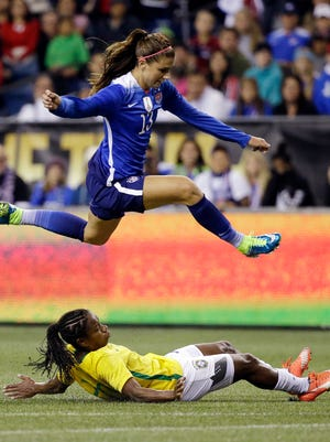 United States' Alex Morgan leaps over Brazil's Formiga during the first half an international friendly soccer match Wednesday, Oct. 21, 2015, in Seattle. The match ended in a 1-1 draw. (AP Photo/Elaine Thompson)