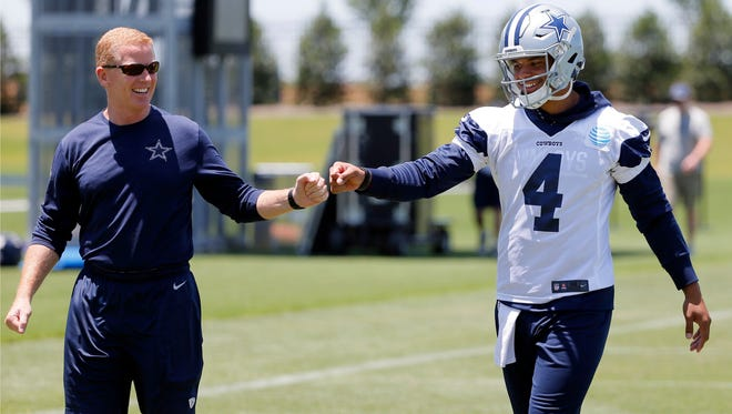 Dallas Cowboys head coach Jason Garrett, left, gets quarterback Dak Prescott (4) a fist bump as the two walk off the field after an NFL football organized team activities practice at the team's training facility, Wednesday.