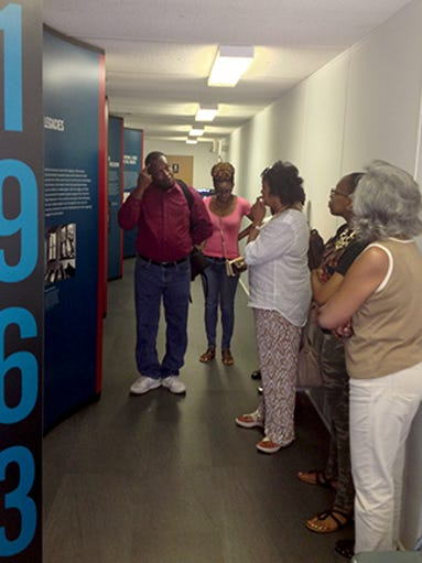 """Pictured, background far left, Dr. Learotha Williams Jr. leads a tour of the """"Changing America"""" exhibit May 30 afternoon in the Promise Land Historic Site annex."""