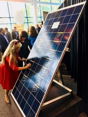 Barbara Quinones, director of the Homestead Electric Utilities Department, signs a ceremonial solar panel commemorating the creation of the Florida Municipal Solar Project.