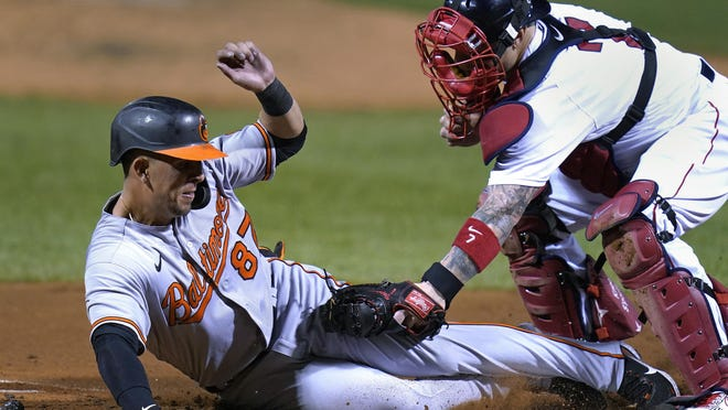 Ramon Urias slides in safely ahead of a Christian Vazquez tag at the plate Thursday night.