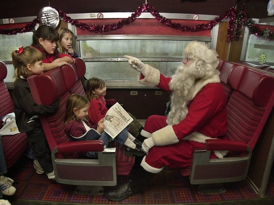 Santa Claus (Bill Lockwood of Shortsville) asks children what they want for Christmas during a Santa Train outing in 2002.