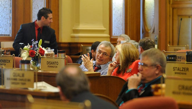 Rep. Lee Schoenbeck talks with Lynne DiSanto before Gov. Dennis Daugaard gives the State of the State address at the state capitol in Pierre, S.D., Tuesday, Jan. 12, 2016.
