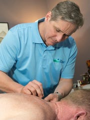 Robert Balko, owner of The Atlantic Center for Acupuncture and Oriental Medicine, performs acupuncture on a patient in his Belmar office.