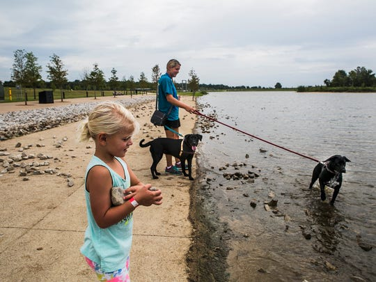 August 30, 2017 - Hadley Allen, 5, prepares to throw rocks into Hyde Lake as her mom, Katie, dog sits Bacchus, center, and Paxton, right, during a visit to Shelby Farms Park, which reopened following a $52 million improvement project on Sept. 1, 2016.