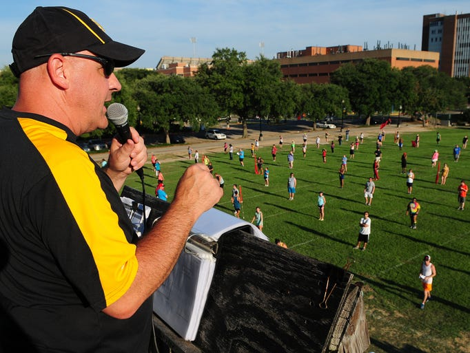 Jamie Standland, director of the Pride of Mississippi marching band, talks with members before running through a portion of the pre-game show on Pride Field during the first day of band camp at Southern Miss.
