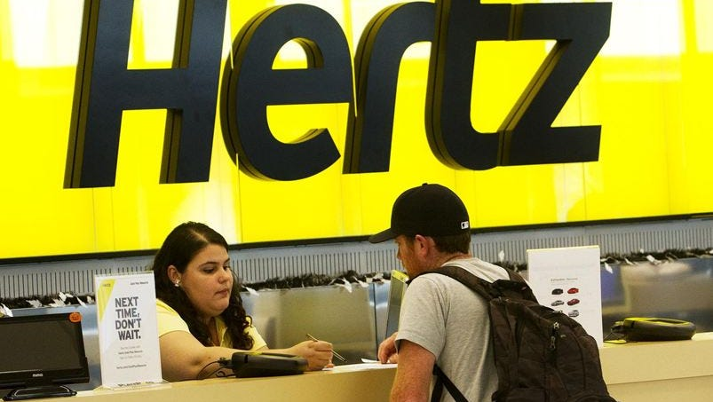 A Hertz employee helps Joe Shanahan, from Cape Cod as he rents a vehicle from the rental car giant on Oct. 24, 2013.