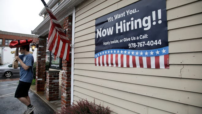 A sign advertising employment hangs outside a restaurant in Middleton, Mass. The number of Americans applying for unemployment benefits rose by 12,000 the week of Sept. 18, to 272,000 as Florida continued to absorb the economic impact of Hurricane Irma.