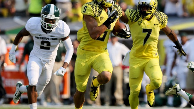 With Michigan State's Darian Hicks, left, in pursuit, Oregon's Devon Allen, center, runs to the end zone with teammate Keanon Lowe providing blocking during the second quarter Saturday.