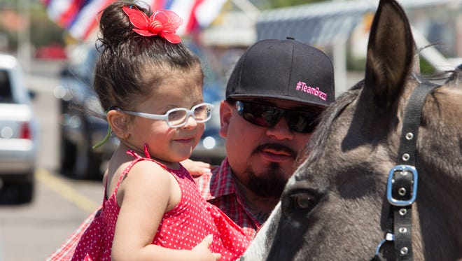 Brezzianna Zapata, 2, and her father Emilio pet a horse at a Team Brezzi fundraiser held on May 7, 2017 at Mesilla Park Healing Arts.