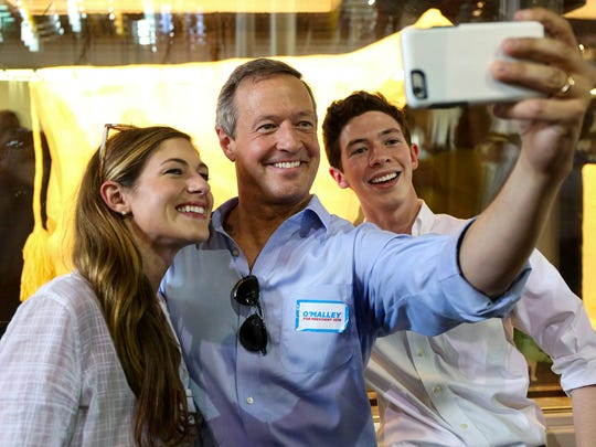 Democratic presidential candidate Martin O'Malley snaps a selfie in front of the Butter Cow at the Iowa State Fair with two of his children, Grace and William, on Thursday, Aug. 13, 2015, in Des Moines, Iowa.