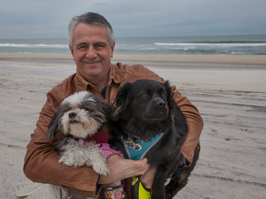 Vince Stango with his dogs Dulce and Luka as they finish their regular walk on the beach in Harvey Cedars. Vince found a bottle with a message in it during a walk just after last week's Nor'easter.