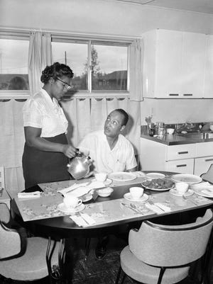 William Myers is served coffee by his wife, Daisy, in their new home in Levittown, Pa., Aug. 19, 1957, as they become the first black family to move into the 15,000-home all-white community. The Myers moved in despite protests by their new neighbors.