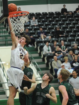 Wylie's Dylan Isenhower, left, drives for a basket while Iowa Park's Nathan Eaves (20), Billy Pearson (4) and another teammate defend. Wylie beat the Hawks 78-43 in a Region I-4A bi-district game Monday, Feb. 20, 2017 in Breckenridge.