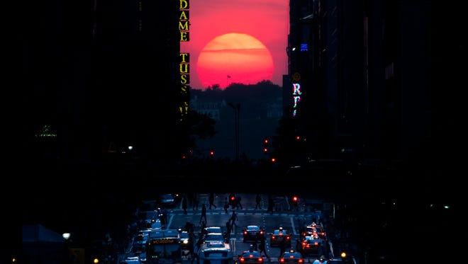 "The sun sets along 42nd Street in Manhattan during an annual phenomenon known as ""Manhattanhenge,"" when the sun aligns perfectly with the city's transit grod, Wednesday, May 29, 2013, in New York."