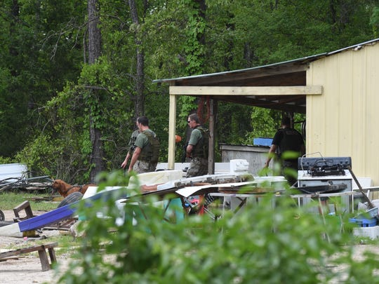 Members of the Arkansas Department of Corrections dog team leave a shed after searching Monday. Several law enforcement officers were on Wild Fern Lane in southern Baxter County pursuing two suspects who ran from law enforcement. One suspect remained at large as of late Monday afternoon.