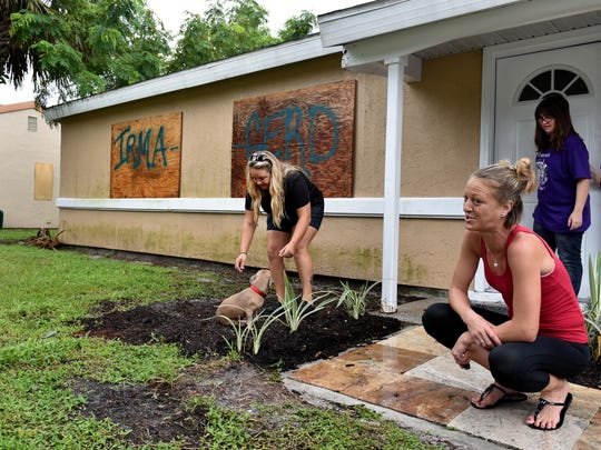 Bridgett Kellett (from left) plays with their dog Munch, along with her sisters Danielle and Chloe as they wait for the arrival of Hurricane Irma while at their home on SW Cherryhill Road on Saturday, Sept. 9 in Port St. Lucie.