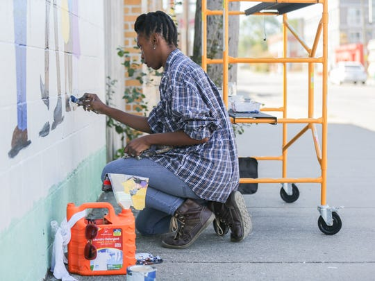 Ajia Coleman Durham works to finish a mural project along 16th St. across from the PreEnactIndy temporary storefronts on Monday, Oct. 2, 2017. PreEnactIndy Indy will take place near the intersection of E. 16th St. and E. Yandes St. on Saturday, Oct. 7, 10 am-5 pm.