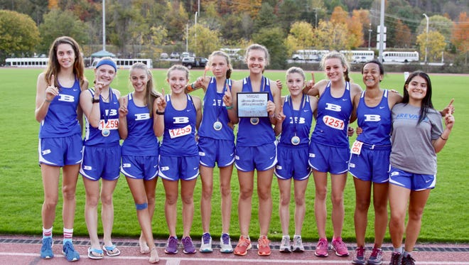 Brevard senior Eliza Witherspoon (pictured in the middle holding a certificate) has accepted a preferred walk-on roster spot with the Alabama cross country and track programs. She has helped lead the Brevard girls to back-to-back NCHSAA 2-A cross country championships.