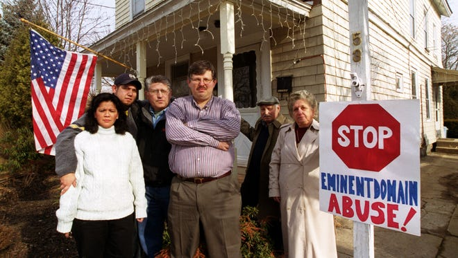 A family stands outside their 1901 home, which was seized for commercial development in New London, Conn. (2000) Today, the seized property is barren.