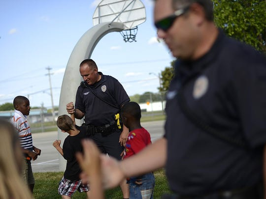 Green Bay community police officers Craig Carlson, left, and Mark Strojny, right, have some fun as they visit with children at Eastman Park in the Olde North neighborhood in Green Bay on Tuesday, July 7, 2015.