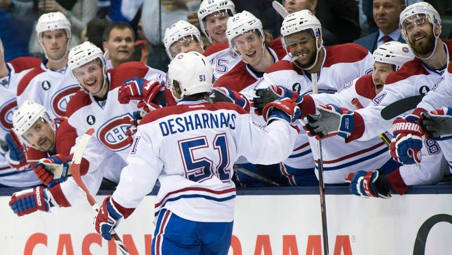 Montreal Canadiens center David Desharnais (51) is congratulated by teammates after scoring the game winning goal during an overtime shootout in an NHL hockey game, Saturday in Toronto.