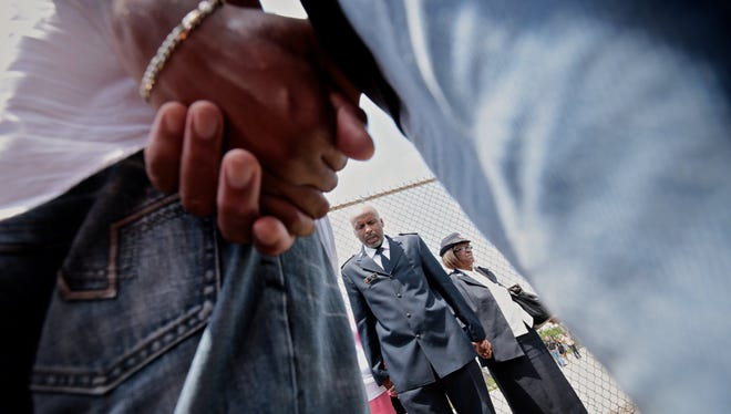 Pastor Artee Lewis, of Detroit Temple Salvation Army Corp, says a prayer along with other church members on Sunday, June 21, 2015 at the scene where 12 people were shot and one confirmed dead.