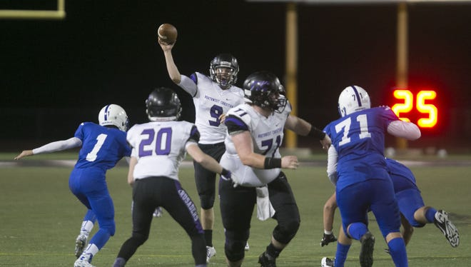 Northwest Christian's Drew Inness (9) throws a pass under pressure from Pusch Ridge's Grayson Barghols (1) during the Division IV State Championship at Chaparral High School on Nov. 28, 2015 in Scottsdale Ariz.