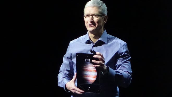 Apple CEO Tim Cook addresses the crowd at an Apple event in 2015, holding a new iPad Pro