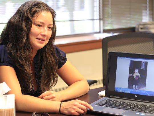 Sarama Teague looks through photos of her sister, Sabrina