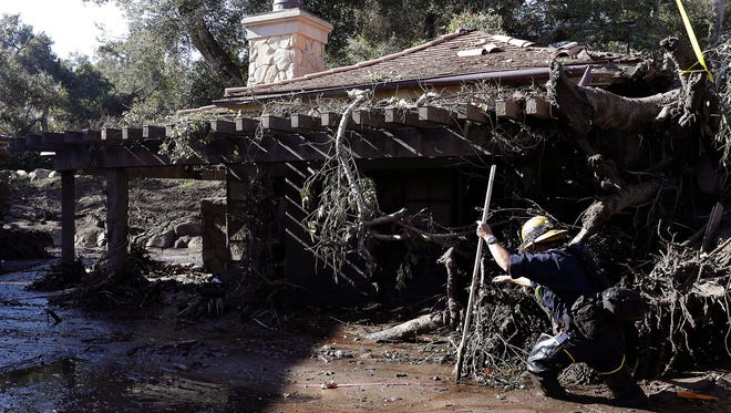 Alex Broumand of the Montecito Fire Department walks in mud in front of homes damaged from storms in Montecito, Calif., Thursday, Jan. 11, 2018. Rescue workers slogged through knee-deep ooze and used long poles to probe for bodies Thursday as the search dragged on for victims of the mudslides that slammed this wealthy coastal town.