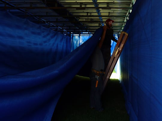 Francisco Gomez of T&B Equipment Company pulls blue mesh to line the ceiling of a walkway tunnel behind the grandstands along the 18th green of the Dinah Shore Tournament Course at Mission Hills Country Club in Rancho Mirage, Calif. on Tuesday, March 24, 2015. Gomez and colleagues are adding a splash of color to the course in preparation for next week's ANA Inspiration LPGA tournament. In previous years as the Kraft Nabisco Championship the grandstands and walkway tunnels were lined with red.