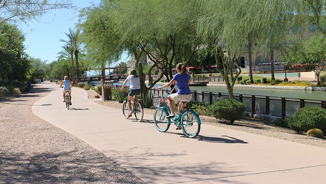 Bicyclists ride along the canal in Phoenix.